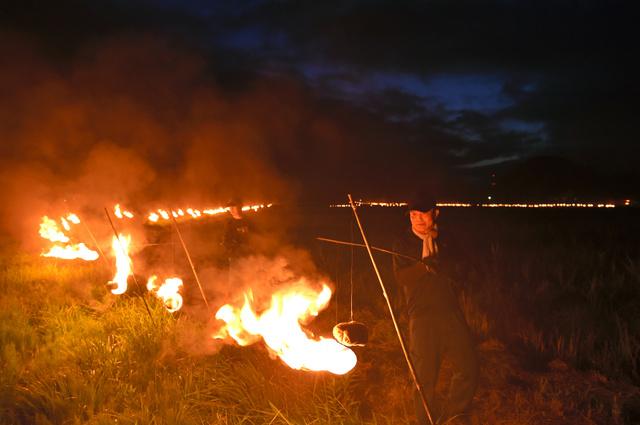 「火の祭」で、あぜ道などにかがり火がともされた=24日午後7時37分、南相馬市小高区、福留庸友撮影