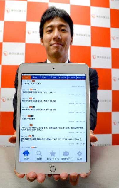「ポケ弁」の画面を開いたタブレット端末を手にする安井弁護士=東京都千代田区