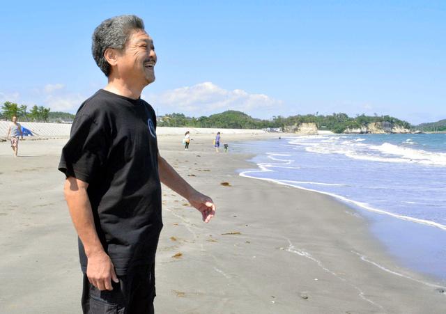 菖蒲田海水浴場の海を眺める岩本喜治さん。海開きを待ちきれない人々が波打ち際を歩く=七ケ浜町