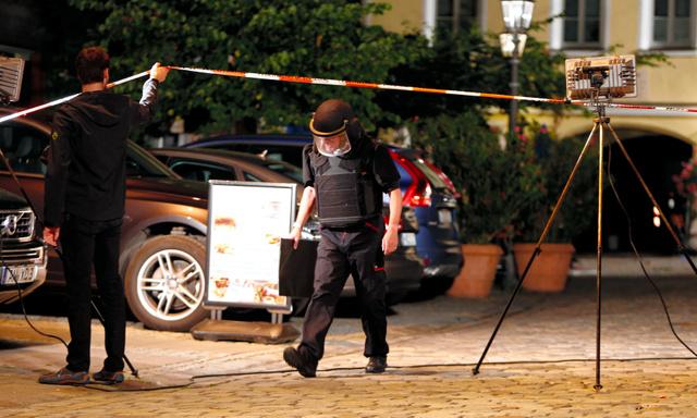 25日、ドイツ南部バイエルン州アンスバッハの音楽祭の会場近くで起きた爆発事件の後、警戒する警察官=ロイター