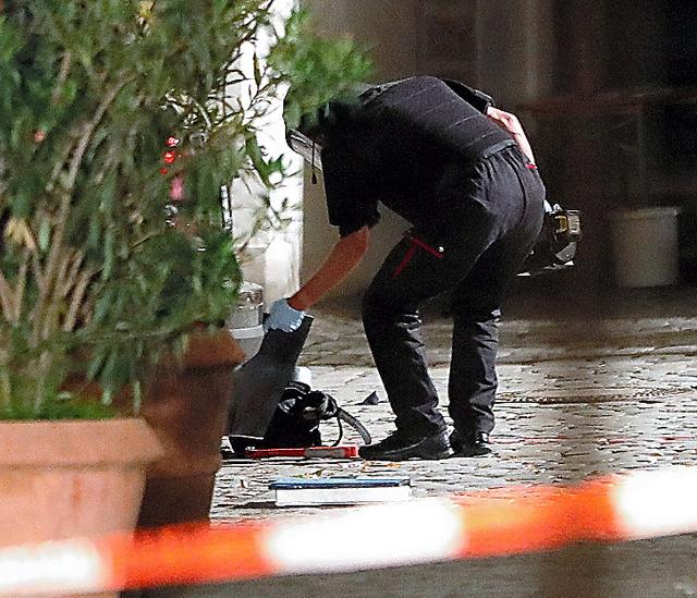 25日、ドイツ南部バイエルン州アンスバッハの音楽祭の会場近くで起きた爆発事件の後、現場に落ちていたリュックサックを調べる警察官=AP