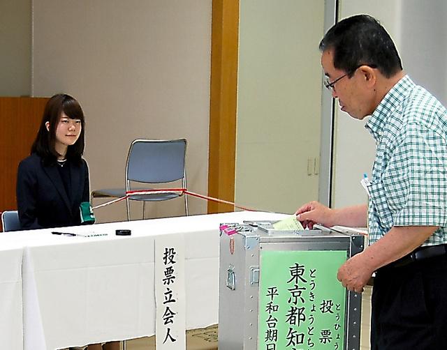 期日前投票所で立会人を務める平野繭子さん(左)=23日、東京都練馬区、杉山麻里子撮影