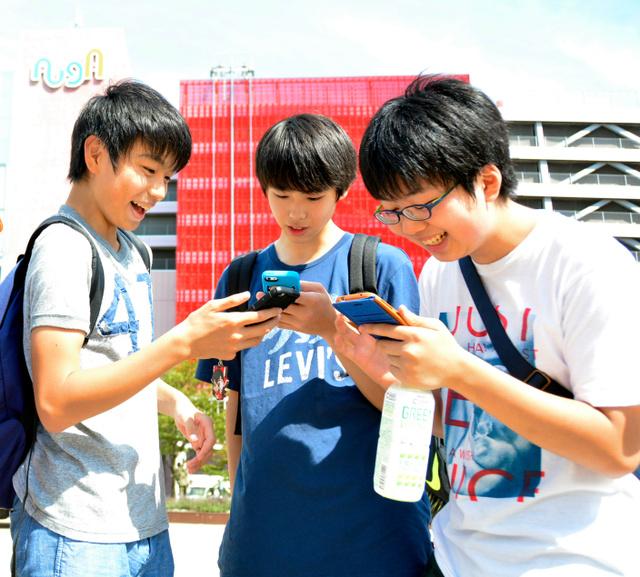 レアなポケモンを見つけて喜ぶ中学生=青森市の青森駅前公園