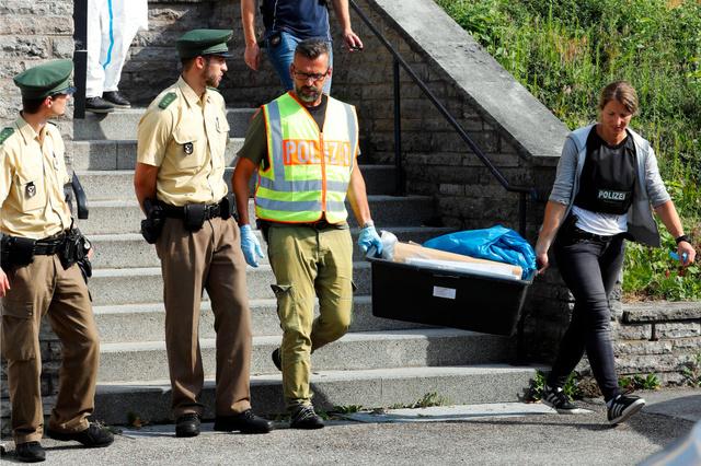 ドイツ南部アンスバッハで25日、自爆したシリア人の男が住んでいた場所から出てくる警察官ら=AP