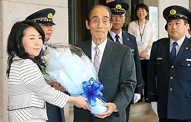 花束を贈られ、国会を後にする輿石東参院副議長(中央)=時事