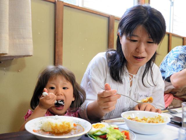 子ども食堂「楽」でカレーを食べる親子=山形市小白川町