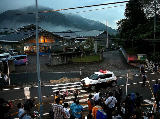 事件現場の施設では、暗くなっても警察車両などの出入りが続いた=26日午後6時55分、相模原市緑区、恵原弘太郎撮影