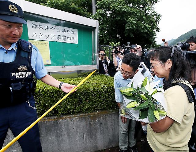 事件があった「津久井やまゆり園」に花束を持って訪れた人=26日午後5時16分、相模原市緑区、岩下毅撮影