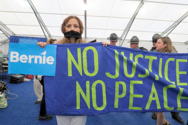 米民主党大会の会場近くで、口に布を巻き無言で抗議するサンダース氏の支持者=フィラデルフィア、五十嵐大介撮影