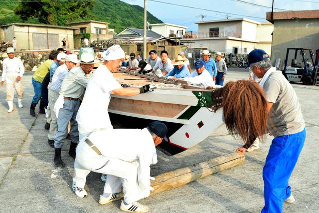 櫂伝馬船を運ぶ島民たち=上関町祝島