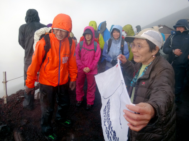 強い雨がたたきつける中、田部井淳子さんが高校生を励ました=富士宮ルート7合目