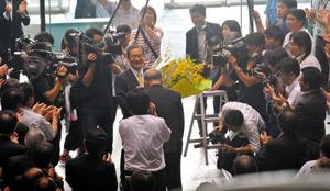 職員から花束を受け取り、大きな拍手で見送られた伊藤知事=27日、県庁