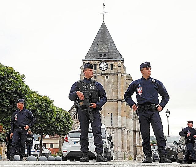 仏北西部ルーアン近郊で27日、襲撃事件の起きた教会の前で警備にあたる警察官ら=ロイター