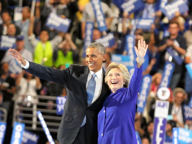 民主党全国大会で、オバマ大統領の演説後に登場したクリントン前国務長官が共に笑顔で代議員らに手を振った=27日、フィラデルフィア、佐藤武嗣撮影