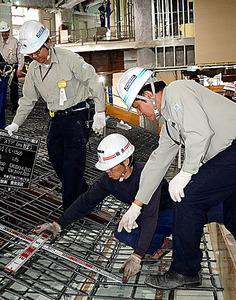 フィリピン出身のソラノ・ジャンさん(右)。現場監督として作業員に指示を出す=東京都千代田区