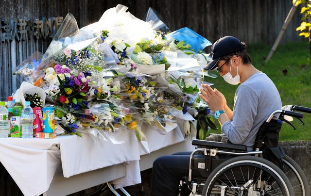 車いすで献花台を訪れ、手を合わせる人=29日夕、相模原市緑区、角野貴之撮影