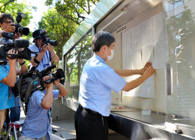 検察審査会の議決書を張り出す検審の事務官=東京・霞が関の東京地裁