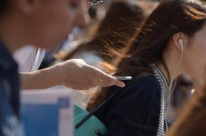 歩きながらスマートフォンに触れる人たち=東京都渋谷区