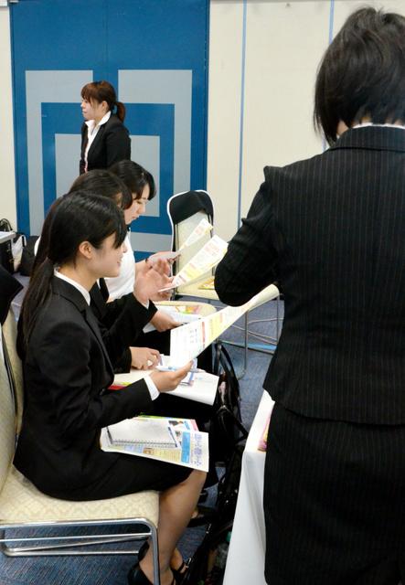 企業合同説明会で採用担当者の説明に耳を傾ける女子学生たち=鹿児島市内