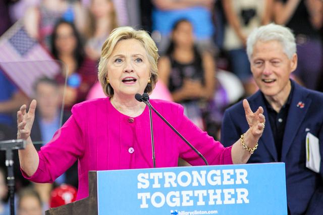 民主党の大統領候補の指名を受諾後、最初の集会で演説するクリントン前国務長官(左)。夫のビル・クリントン元大統領が見守った=7月29日、フィラデルフィア、ランハム裕子撮影