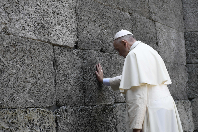 ポーランド・アウシュビッツ強制収容所跡で29日、多数が銃殺された「死の壁」の前で祈る法王。オッセルバトーレ・ロマーノ提供=AFP時事