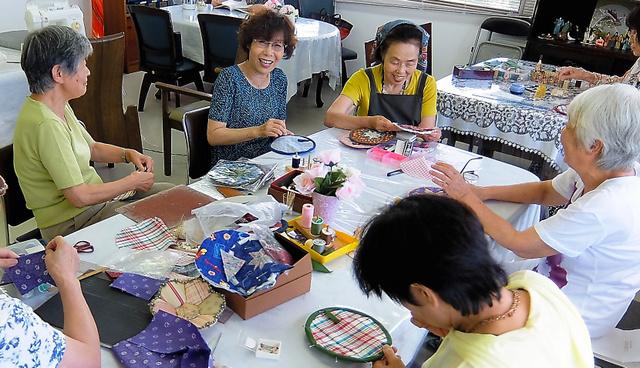 交流施設でパッチワークを楽しむ参加者とボランティアたち=大阪府茨木市の「街かどデイハウス 山手台ななつ星」