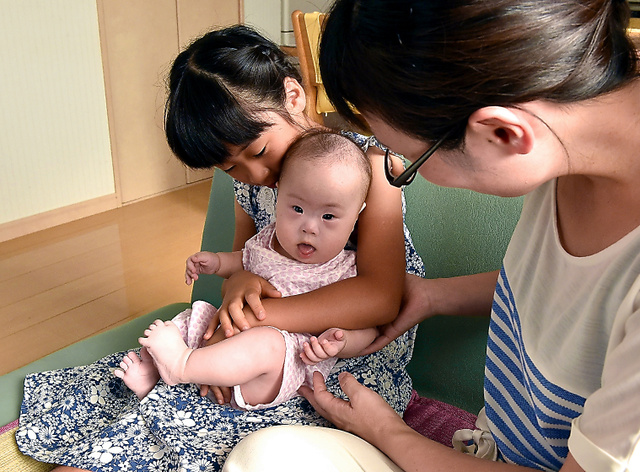 熊本地震を乗り越えて、自宅に戻ってきた友田さくらちゃん(中央)。母の晴美さんが見守る中、姉の萌々香(ももか)さんに抱かれ、ほほえんだ=7月29日、熊本市南区、福岡亜純撮影