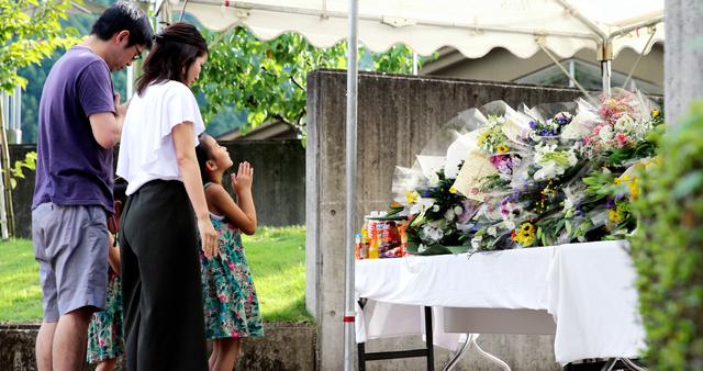 「津久井やまゆり園」の前で献花し、手を合わせて犠牲者を悼む人たち=1日午後3時36分、相模原市緑区千木良、越田省吾撮影