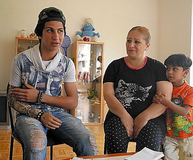 右腕に義手を付けて取材に応じるアナス・ユーナスさん(左)。母ナハラさん(中央)や弟たちと平穏な暮らしを取り戻した=ハノーバー近郊、玉川透撮影