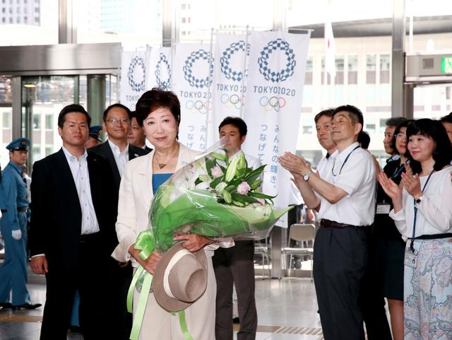 職員から贈られた花束を手に、東京都庁に入る小池百合子氏=2日午前9時32分、東京都新宿区、遠藤啓生撮影