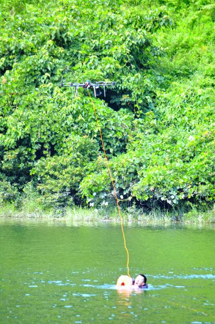 ドローンから下ろされた浮輪につかまる要救助者=鳥栖市の河内ダム
