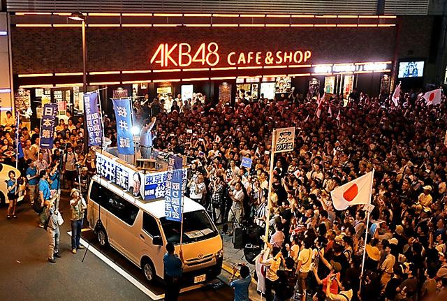 選挙戦最後の夜、JR秋葉原駅前での桜井誠氏の街頭演説。支持者らが日の丸を手に集まった=7月30日夜
