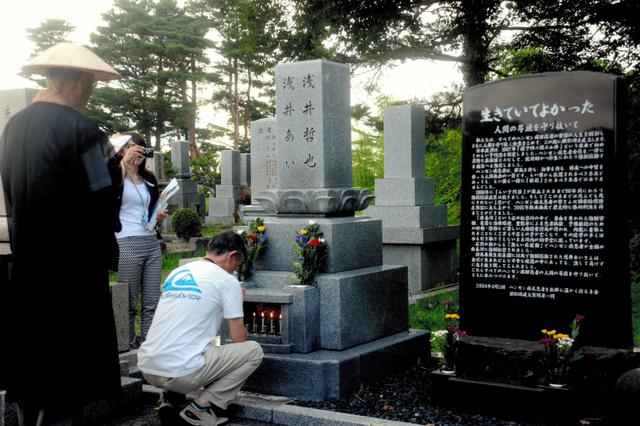 浅井あいさんの墓前を訪れた人たちが順番に焼香して手を合わせた=金沢市若松町