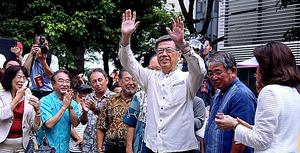 約1500人(主催者発表)が参加した開廷前の集会で、手を上げて応える沖縄県の翁長雄志知事=5日午後1時32分、那覇市