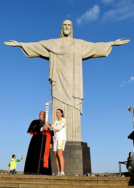 リオデジャネイロ五輪の開会式を迎える5日の早朝、聖火リレーが市内の観光名所・コルコバードの丘にあるキリスト像(高さ30メートル)付近を通過した。標高710メートルの丘の上に聖火のトーチを持ったランナーが到達し、朝日を浴びた像をバックにポーズをとった(諫山卓弥)