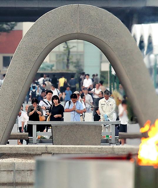 早朝から原爆死没者慰霊碑の前で手をあわせる人たち=6日午前5時26分、広島市中区の平和記念公園、上田潤撮影