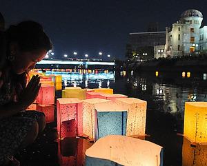 平和を願い、元安川に灯籠(とうろう)を流す人=6日夜、広島市中区、加藤諒撮影