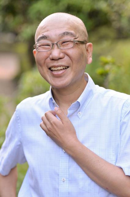 同僚と笑顔で雑談する筆者=8月5日、東京都中央区築地の朝日新聞東京本社で、瀬戸口翼撮影
