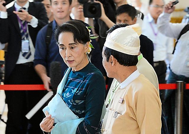ミャンマー国会で3月15日、記者団の問いかけに応じず議場を後にするアウンサンスーチー(左)=ネピドー、五十嵐誠撮影
