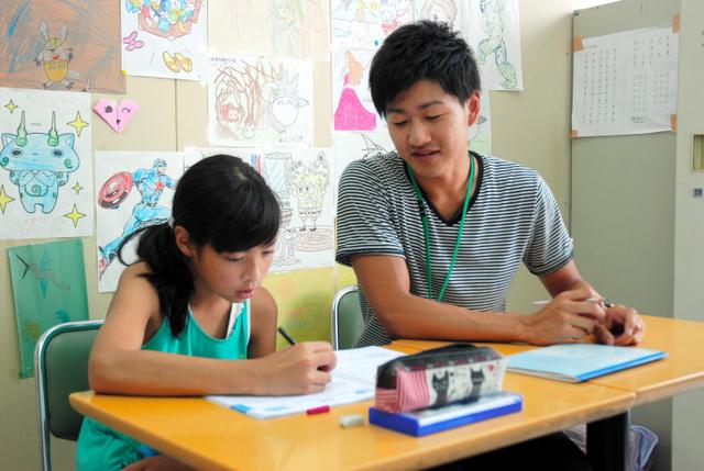 上智大学の学生に手伝ってもらいながら夏休みの宿題に取り組む日系ブラジル人の小学生=大泉町西小泉