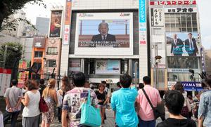 東京都新宿区で8日、大画面に映し出された天皇陛下のビデオメッセージに見入る人々=AP