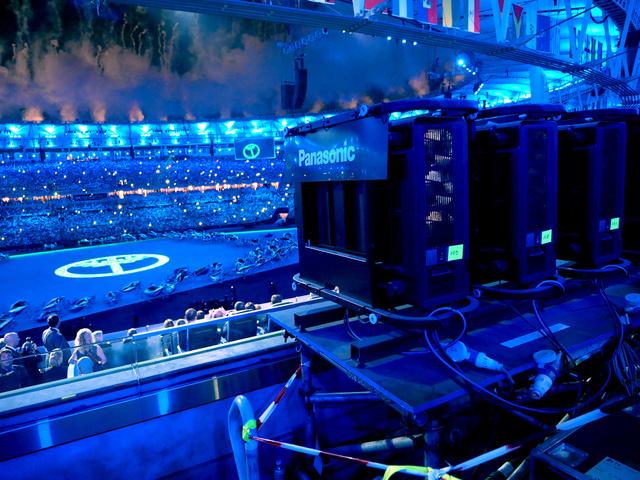 開会式で、スタジアムの客席後方に並んだパナソニックの高画質プロジェクター(右)。会場中央に様々な光の演出を投影した(同社提供)