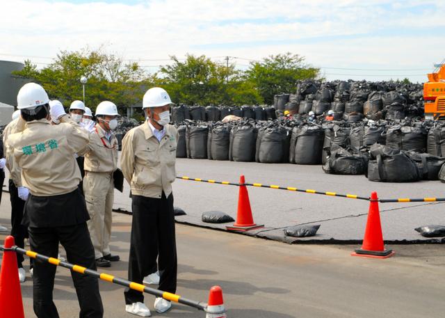 汚染土の袋が運び込まれた中間貯蔵施設予定地を視察する山本公一環境相=大熊町