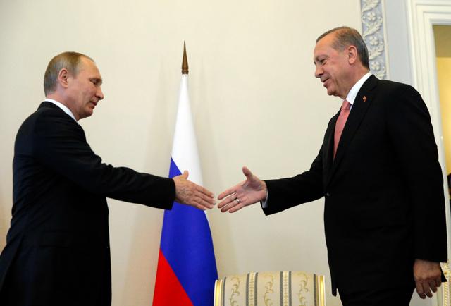 ロシア・サンクトペテルブルクで9日、首脳会談で握手するロシアのプーチン大統領(左)とトルコのエルドアン大統領=AP