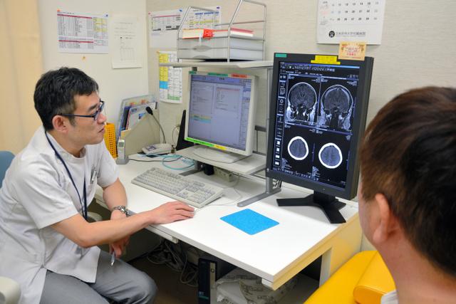 連載で紹介した東裕也さんは主治医の佐藤俊さんからMRI画像の説明を受けた=東京都文京区の日本医大病院