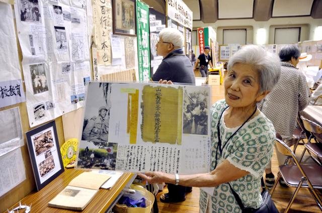 ガダルカナル島で戦死した兄の遺影を手に語る梶浦さん=名古屋市昭和区の市公会堂