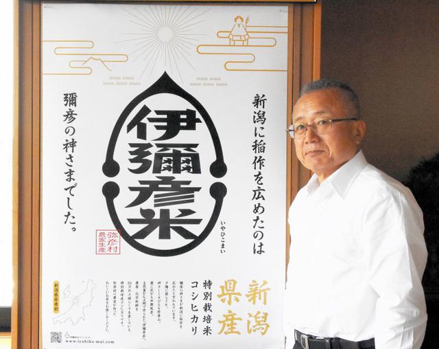 伊彌彦米のポスターの前に立つ小林村長