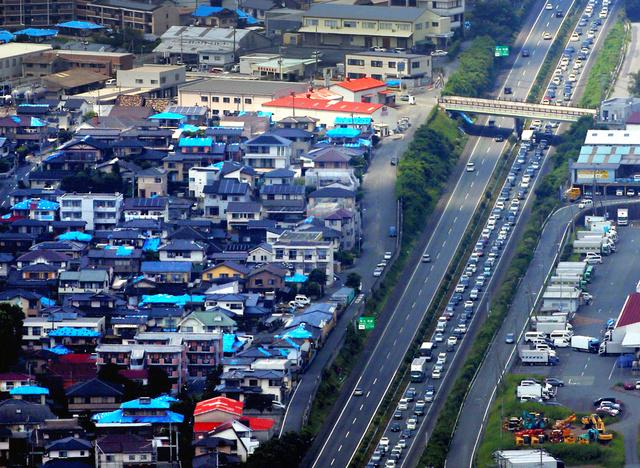渋滞する九州自動車道の下り線熊本IC付近。周辺にはブルーシートがかかったままの住宅が数多く残っている=13日午後1時8分、熊本市東区、朝日新聞社ヘリから、上田幸一撮影
