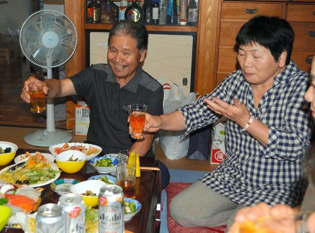 妻や親類とともに宿泊を乾杯で喜び合う佐藤右吉さん(左)=大熊町大川原