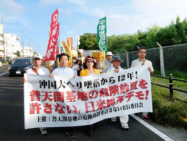 米軍普天間飛行場のフェンス沿いをデモ行進する抗議集会の参加者たち=沖縄県宜野湾市